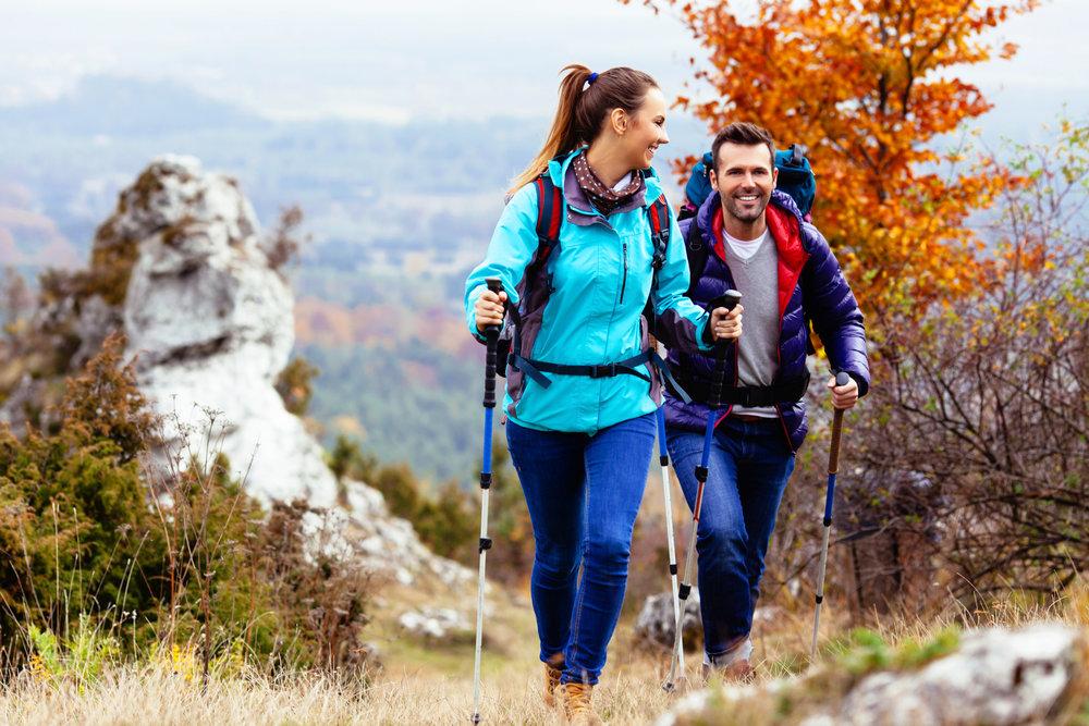 мужчина и женщина идут по горам с палками и рюкзаками