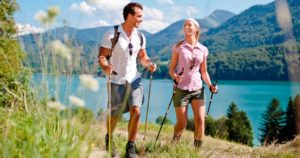 мужчина и женщина идут с палками для ходьбы