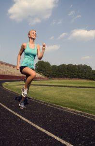 девушка бежит по стадиону