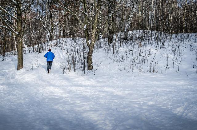 мужчина бежит по зимнему лесу